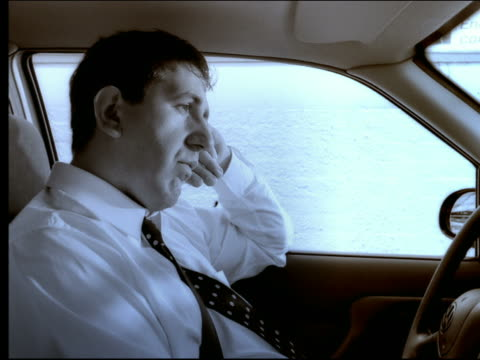 Tired businessman in car waiting in traffic