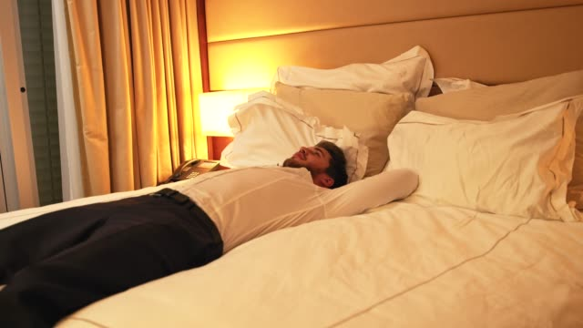 tired businessman jumping on the bed in hotel room - telecamera traballante video stock e b–roll