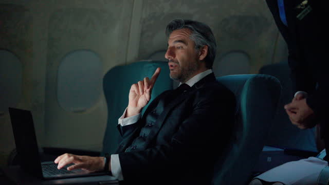 vídeos de stock e filmes b-roll de tired businessman using laptop computer on private jet airplane during the night flight. - elegante