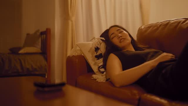 仕事の後に家に到着し、ソファの上で休んでいる間、暖かいトーンにライトの色を回すようにスマートスピーカーを注文する疲れたビジネスウーマン - 到着点の映像素材/bロール