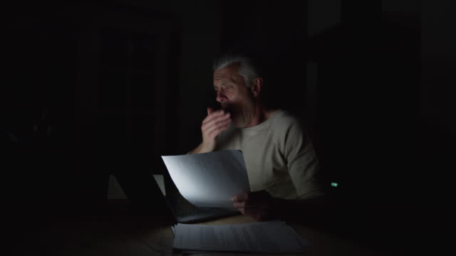 tired caucasian man working late at night looking at laptop and documents - paperwork stock videos & royalty-free footage