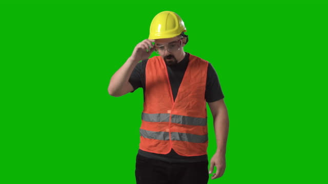 tired construction worker taking off his hardhat and clothes resting chroma green screen background - helmet stock videos & royalty-free footage