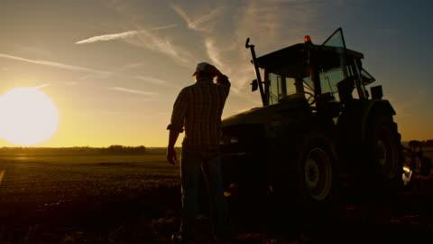 stockvideo's en b-roll-footage met ws moe landbouwer na een lange dag van hard werken - tractor