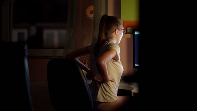 vídeos y material grabado en eventos de stock de mujer freelance cansada trabajando en un nuevo proyecto por la noche con dolor de espalda durante la pandemia covid-19 - dolor de espalda
