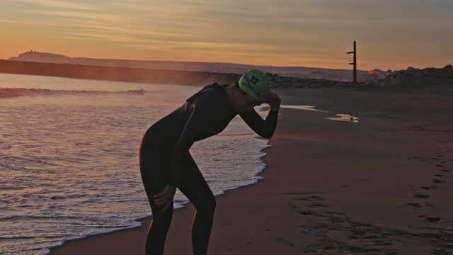 "tired female triathlete standing on beach after dawn workout - xavierarnau or ""xavier arnau serrat"" stock videos & royalty-free footage"