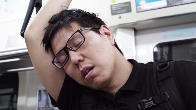 tired guy sleeping while standing up on subway. - sleeping stock videos & royalty-free footage