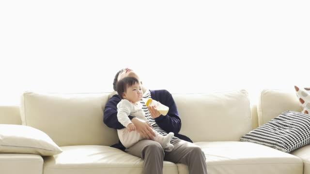 vídeos y material grabado en eventos de stock de a tired korean dad trying to feed a baby with bottle milk - genderblend