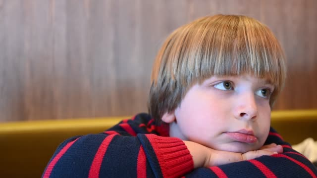 vídeos y material grabado en eventos de stock de tired little boy sitting in a restaurant - recostarse