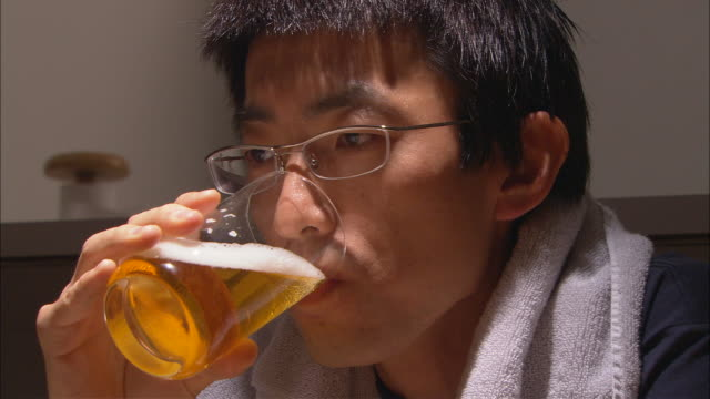 CU, Tired man drinking beer at home