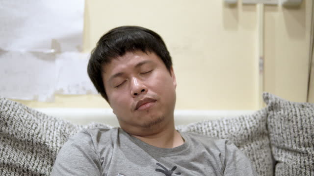 tired man napping on sofa. - laziness stock videos & royalty-free footage