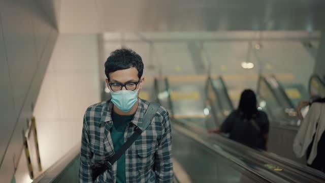 疲れた男性は外科用マスクを着用し、電車で仕事の後に家に帰っています。 - 待つ点の映像素材/bロール