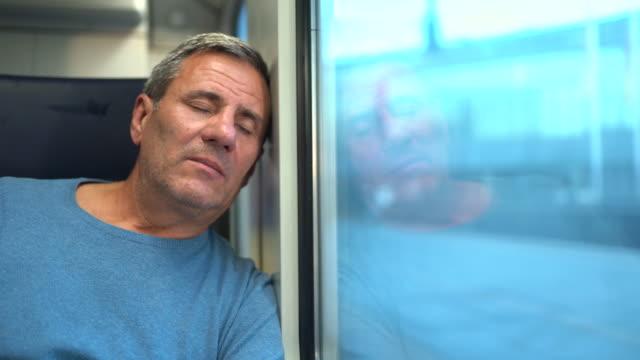 vidéos et rushes de homme mûr fatigué prenant une sieste tout en voyageant dans le train - passenger train