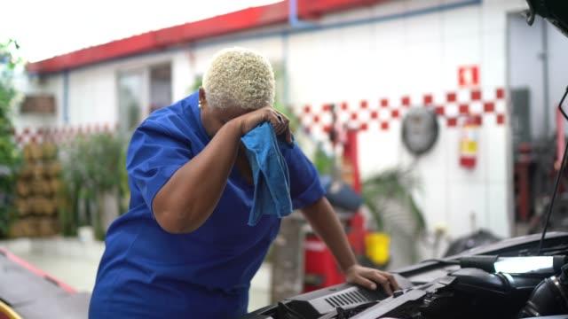 vídeos y material grabado en eventos de stock de mujer mecánica cansada con dolor de cabeza en el trabajo de reparación de automóviles - 40 44 años