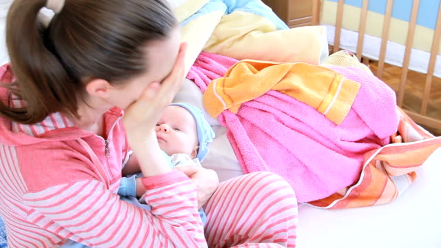 Cansado de la madre y el bebé en sus brazos