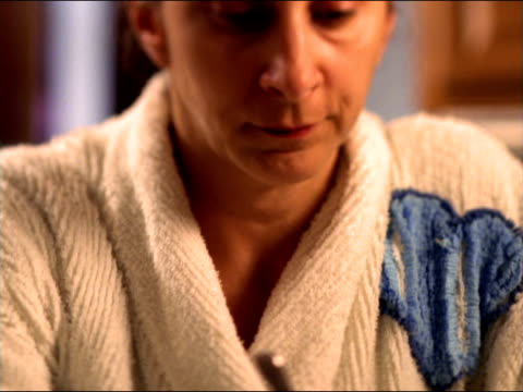 A tired mother dressed in her bathrobe sits at a cluttered table holding her coffee mug.