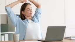 Tired of sedentary work woman stretching body at workplace