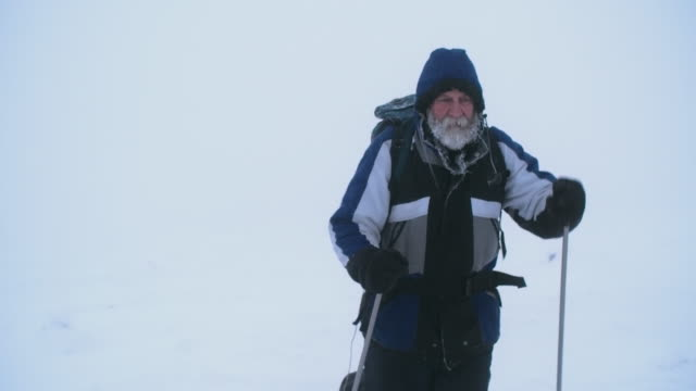 tired old traveler walking in snowshoes - mitten stock videos and b-roll footage