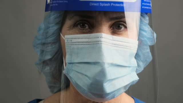 tired, overworked, exhausted health care worker wearing a mask and a face shield posing looking at the camera - female nurse stock videos & royalty-free footage