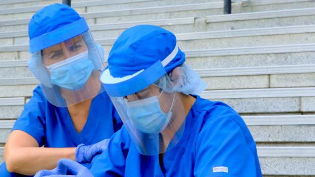休憩中に病院の外に座っている疲れ、過労、疲れ果てた医療従事者 - 盾点の映像素材/bロール