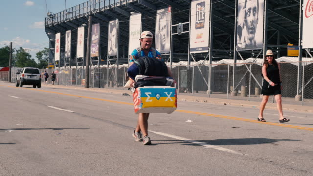 A tired race fan caries a large cooler and sleeping bags on Georgetown Road after the 100th running of the Indianapolis 500 car race at Indianapolis...
