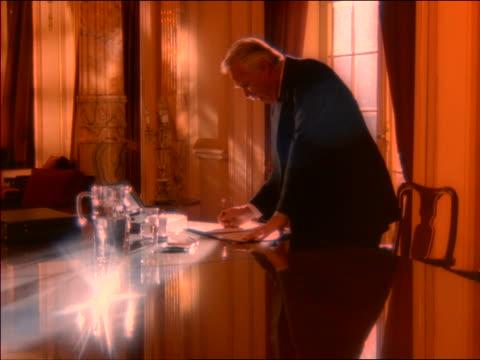 vídeos de stock e filmes b-roll de orange tired senior businessman standing at table in elegant conference room / rubs eyes + sits down - sentar se