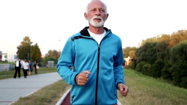 tired senior man running outdoors - peluria del viso video stock e b–roll