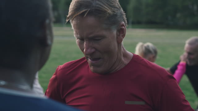 tired senior man talking with female instructor while breathing heavily after workout at park - exhaustion stock videos & royalty-free footage