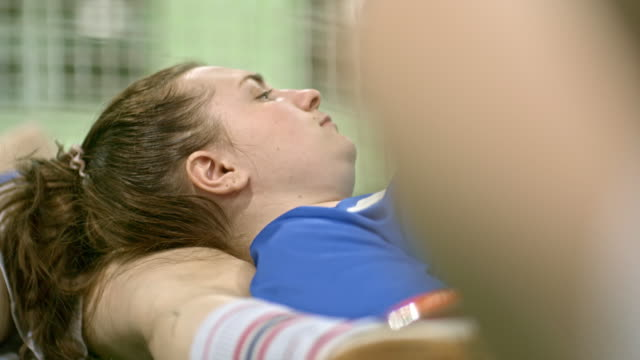 Tired sportswoman lying on teammate after practice