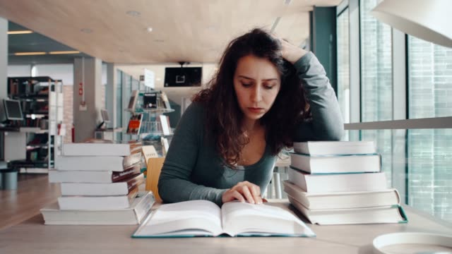 tired student in library - textbook stock videos & royalty-free footage