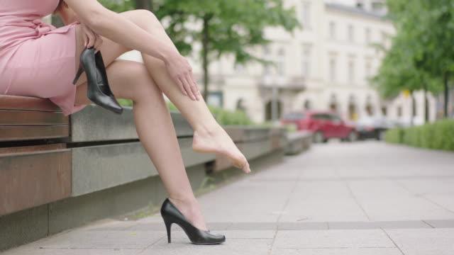 vidéos et rushes de fatigué femme en robe rose, assis sur un banc - jambe