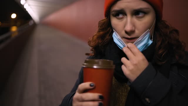 tired woman lowers medical mask to drink coffee wearing xmas hat - coffee drink stock videos & royalty-free footage