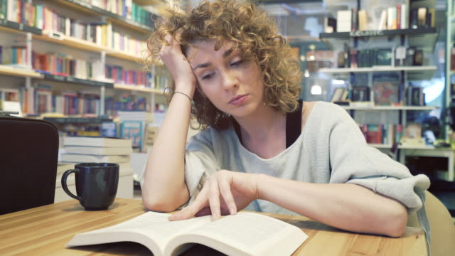 Tired woman reading in a library full of books.