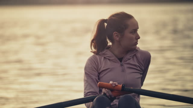 tired woman resting on boat in river at sunset - barca da canottaggio video stock e b–roll
