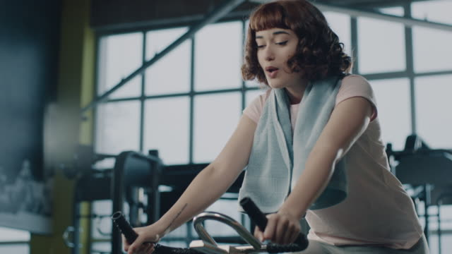 tired woman using spin machine in gym - exercise bike stock videos & royalty-free footage