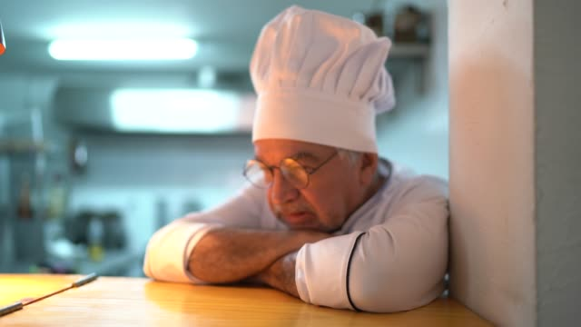 a tired / worried senior chef in the kitchen counter - owner stock videos & royalty-free footage