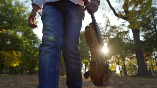 tired young violinist leaving a public park after a performance - violin stock videos & royalty-free footage