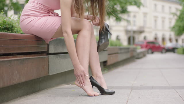 Tired young woman in pink dress sitting on bench and massaging feet
