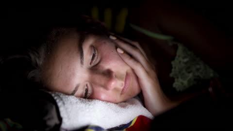 trött ung kvinna om på sidan tittar på smart telefon och försöker få lite sömn - helgaktivitet bildbanksvideor och videomaterial från bakom kulisserna