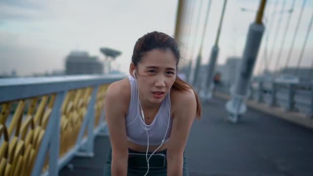 疲れ若い女性橋、スローモーションのジョギングの後にリラックスできます。 - resting点の映像素材/bロール