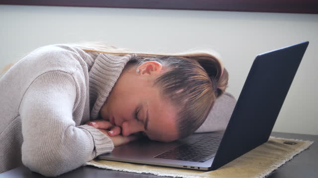 tired young woman sleeping on laptop computer - reminder stock videos & royalty-free footage