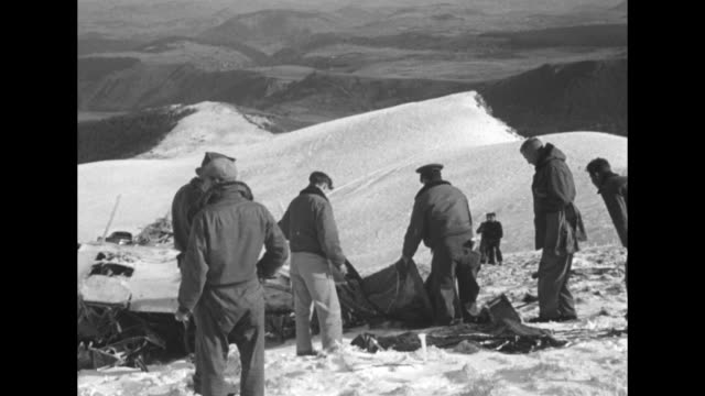 """title """"36 gi's die as flying boxcar hits french peak"""" superimposed over wreckage / wreckage on snow- covered mountaintop, land and mountains beyond /... - partire bildbanksvideor och videomaterial från bakom kulisserna"""