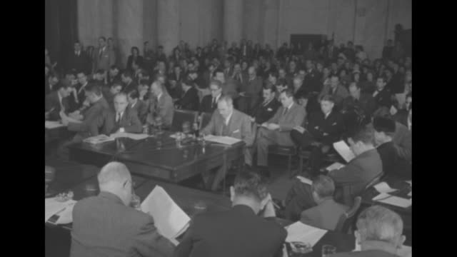 Title 'Acheson urges fast Atlantic pact arms aid' superimposed over US Secretary of State Dean Acheson sitting at desk testifying before committee /...