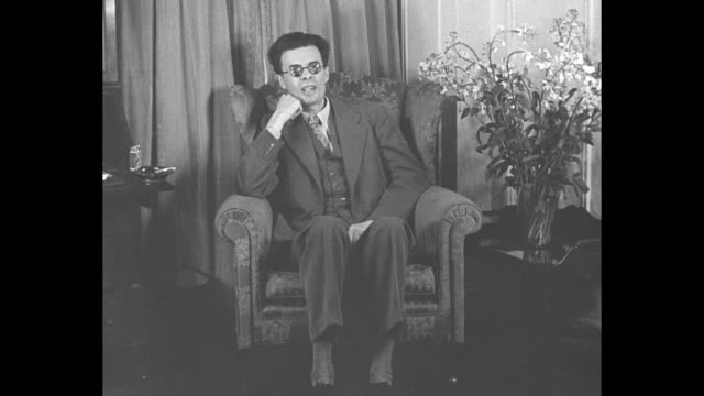 aldous huxley superimposed over author aldous huxley sitting in chair next to large bouquet sot i've come to america for the coronation [of king... - coronation stock videos and b-roll footage