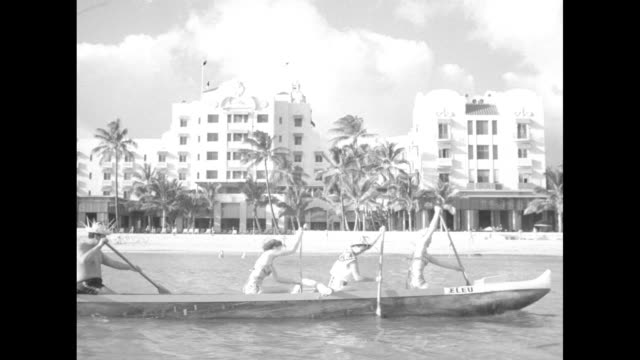 Title Aloha fashions superimposed over shot from behind three models as they stand and look out over Waikiki Beach / two models wearing bathing suits...