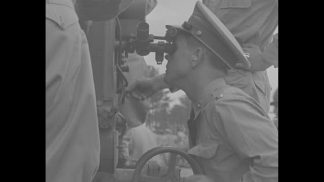 """""""american's answer to air power"""" superimposed on a firing field gun / several views of the guns firing at a target in the air; an officer looks... - an answer film title点の映像素材/bロール"""