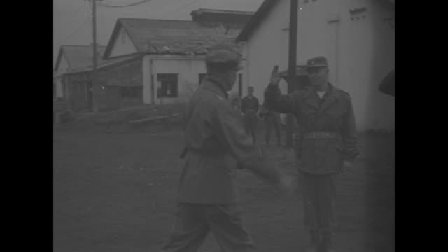 """""""army cameramen decorated in korea"""" superimposed over group of servicemen / maj gen edward m almond walks right and salutes / rows of soldiers at... - first line of defense film title stock videos & royalty-free footage"""