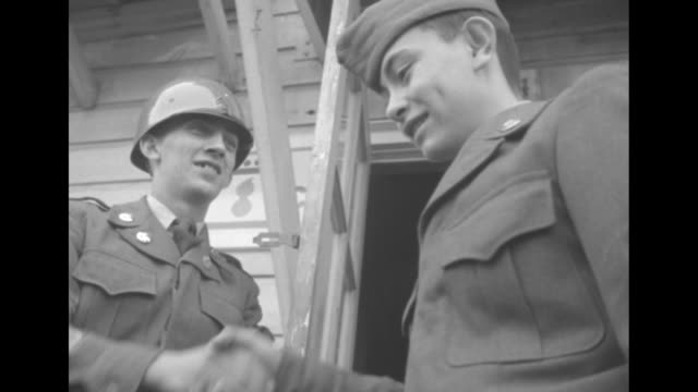 Title Army 'retires' Pvt Raymundo he's only 13 superimposed over Pvt George Raymundo standing on small porch to building shaking hands with soldiers...