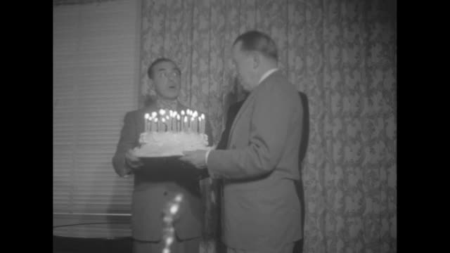Basil O'Connor Marks 30 Years in Polio Fight superimposed over men holding cake / Eddie Cantor presents Basil O'Connor with birthday cake /...
