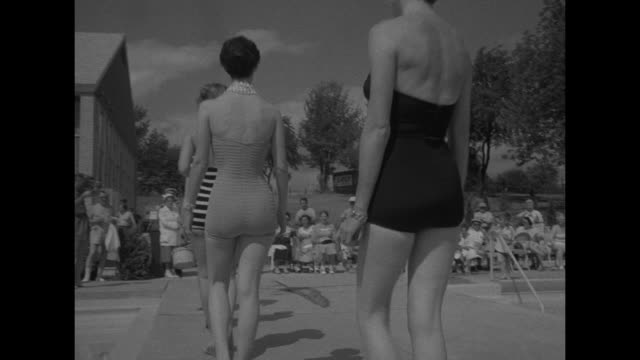 'Bathing suits old new and future' superimposed on women in swimsuits / woman wearing several different style of bathing suits walk past swimming...