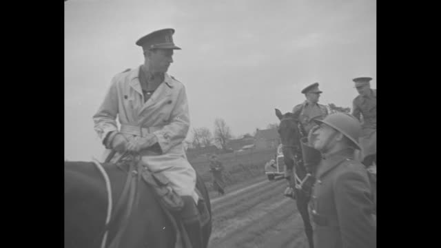 'Belgium' superimposed over Belgian King Leopold III on horseback as he reviews Belgian troops / CU King / quick shot soldiers present arms with...